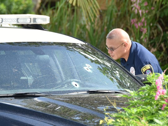 In this file photo, a police officer examines bullet holes in the windshield of a police car on Chalan Langet in Dededo after a shooting that left Steven Camacho Seagraves dead and sent an officer to a hospital. The Guam Police Department has yet to release its policy on use of force or its protocol for officer-involved shootings.