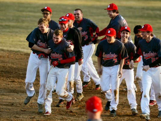 Dover baseball players surround Grant  Hoover (#8, front row, second from left) after his game-winning hit against Susquehannock on Friday, March 21, 2014. Dover overcame Susquehannock's 5-1 lead to win their opening-day baseball game 6-5 at home on Friday, March 21, 2014. Chris Dunn -- Daily Record/Sunday News