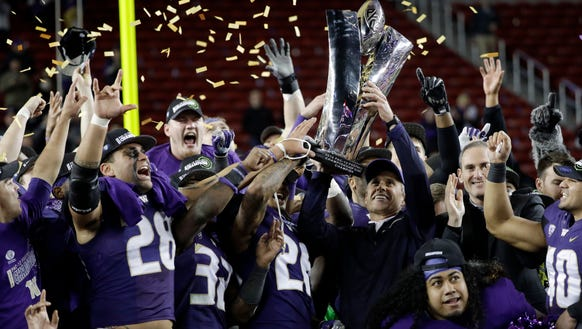 Washington coach Chris Petersen holds the trophy after