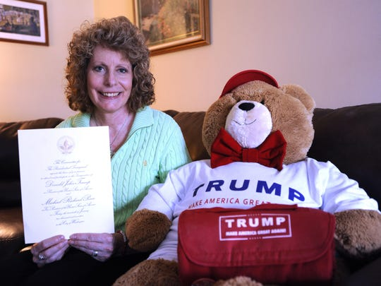 Sandra Haroutunian, 51, of Clinton Township, poses with a bear wearing a Trump T-shirt as she holds the official Presidential Inauguration invitation to the swearing-in ceremony and festivities.