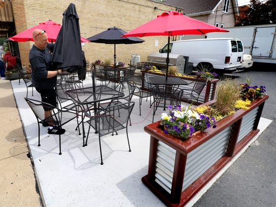 Owner Bob Nicholson sets out umbrellas on a new patio