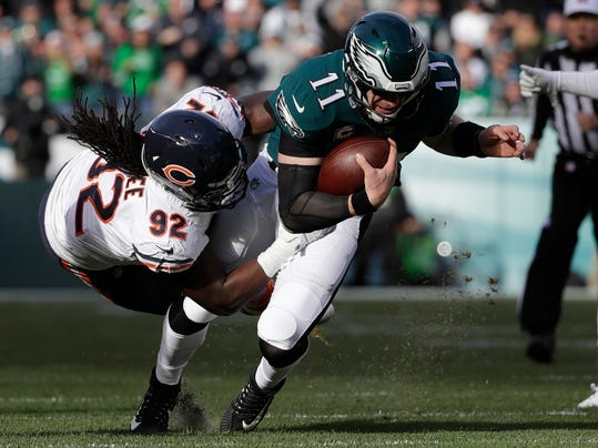 FILE - In this Nov. 26, 2017, file photo, Philadelphia Eagles' Carson Wentz (11) is tackled by Chicago Bears' Pernell McPhee (92) during the first half of an NFL football game in Philadelphia. The Washington Redskins have signed free agent linebacker McPhee. The team announced the deal Monday, March 26, 2018. (AP Photo/Michael Perez, File)