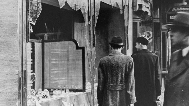 Germans pass by the broken shop of a Jewish-owned business that was destroyed during Kristallnacht.