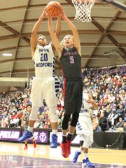 South Salem's Joseph Carey (5) and South Medford's Raymond Benford (20) vie for a rebound in South Medford's 49-48 win in the OSAA Class 6A state semifinals on Friday, March 11, 2016.