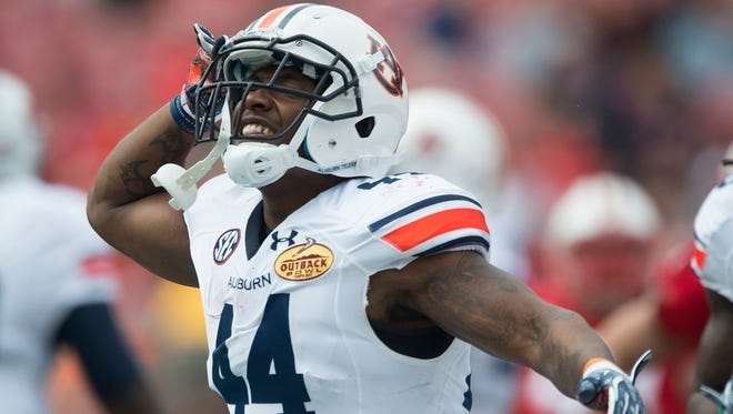 Auburn running back Cameron Artis-Payne salutes after scoring a touchdown during the Outback Bowl between Auburn and Wisconsin at Raymond James Stadium in Tampa, Fla., on Thursday, Jan. 1, 2015.