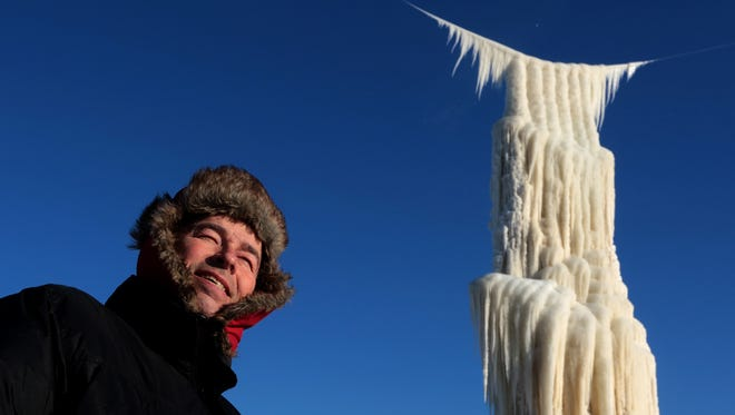 Roger Hanson makes his way past an enormous free-standing ice sculpture he was creating near the shores of Lake Superior in Superior last month. The structure collapsed Tuesday.