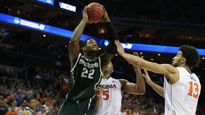 Michigan State's Branden Dawson shoots against the Virginia Cavaliers' Dairon Atkins during second half action at the Time Warner Cable Arena.