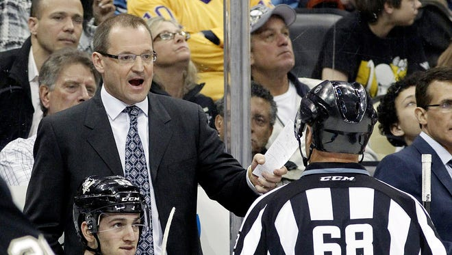 Pittsburgh Penguins head coach Dan Bylsma (top left) reacts to linesman Scott Driscoll (68) after a Penguins goal was disallowed for goal tender interference against the Los Angeles Kings.