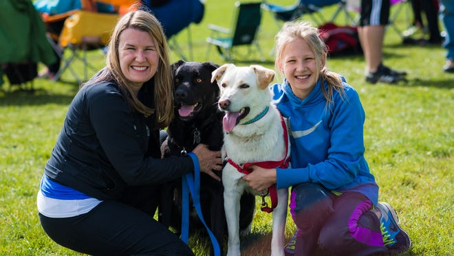 Jennifer with her daughter Skye Vancil and dogs Jake and Sophie cheering on Angus's team.