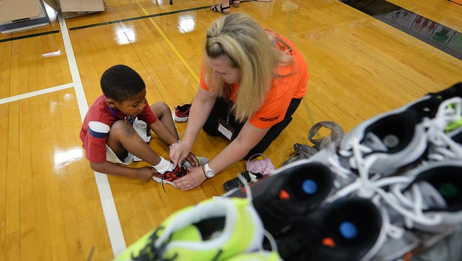 Da Vante Edwards, left, gets help choosing new shoes from volunteer Becky Bradl during the annual Back to School Store at Green Bay East High School.