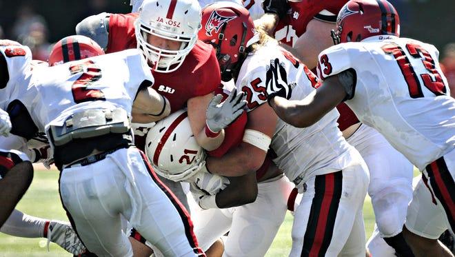 Andrew Jarosz blocks during a St. John's University football game last season. Jarosz is one of three Johnnies tackles who has dealt with injuries this season.