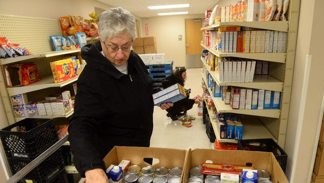 Donna Korb puts together food boxes at the Great Falls Community Food Bank for two families in the St. Martin de Porres food program on Dec. 7.