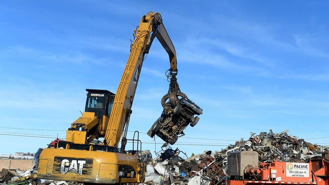 An excavator places a junked car on top of a scrap metal heap for baling at Pacific Steel and Recycling. A lower market price for scrap metal has reduced business for the recycling business.