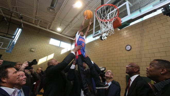 Former Pistons Michael Curry and James Edwards lift Michael Willis, 8, for the ceremonial first dunk after the dedication of the new basketball court in the S.A.Y. Detroit Play Center at Lipke Park in Detroit on Monday, January 18, 2016.