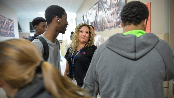 St. Cloud Tech Resource Officer Tara Vargason seems to always be the hub of action in the hallways of the school. A group surrounds her during the fourth hour break between classes near the lunch room Thursday, March 3.