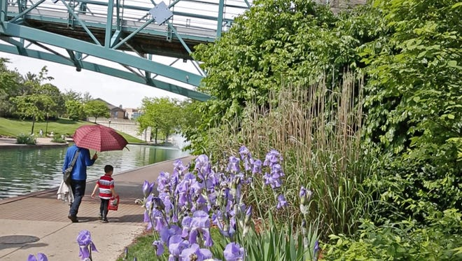 People stroll alongside the downtown Canal, Wednesday, May 11, 2016.