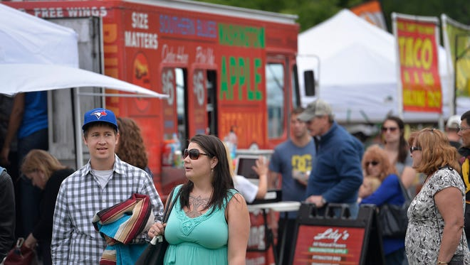 Participants peruse the tents and food trucks that offer a wide variety of food items at Summertime by George!
