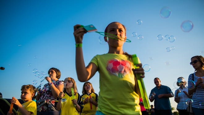 Friends, family and classmates of Codie Powell blow bubbles Saturday night June 25, 2016 during a memorial service in memory of Codie.