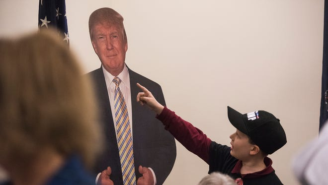 Charles Crotty, 10, of Littlestown points to a cardboard cut-out of President-Elect Donald Trump as Adams County Republicans celebrate at the office of the Adams County Republican Committee.