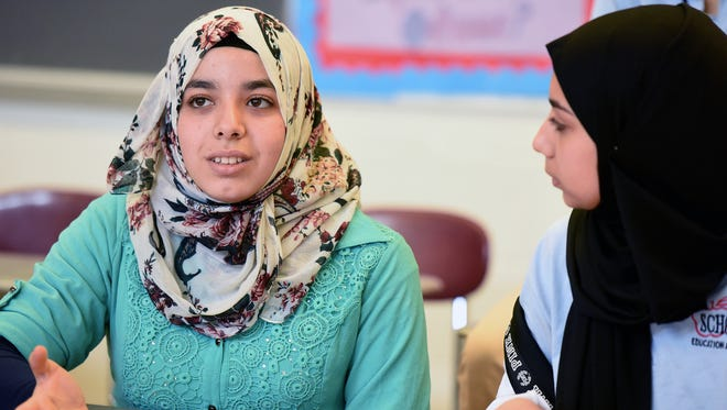 Syrian refugee Fatemah Alkatouf, 16, left, with fellow student Rayah Hammad, discusses participating in the Memory Project with classmates at John F. Kennedy High School in Paterson.