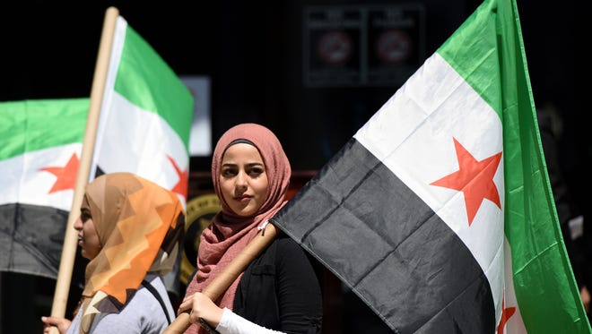 Sisters Noha Alzouabi, 18, and Mariam Alzoubabi, 15, of Paterson attend a Syrian Independence Day ceremony at Paterson City Hall on Sunday. The event celebrates the country's freedom from French rule.