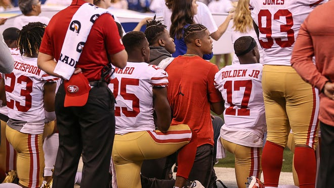 Some players from the San Francisco 49ers kneel during the national anthem, before the game against the Indianapolis Colts at Lucas Oil Stadium in Indianapolis on Oct. 8, 2017.