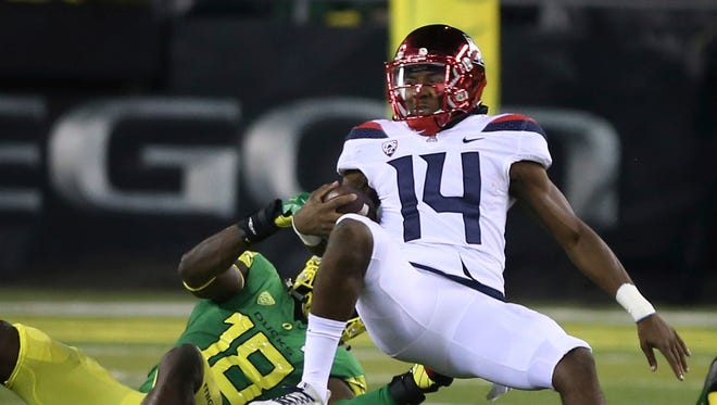 Oregon's Jimmie Swain, left, pulls down Arizona quarterback Khalil Tate during the the fourth quarter of an NCAA college football game, Saturday, Nov. 18, 2017, in Eugene, Ore.
