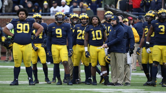 Michigan players, along with defensive coordinator Don Brown, right, in the fourth quarter of the 31-20 loss to Ohio State last year.