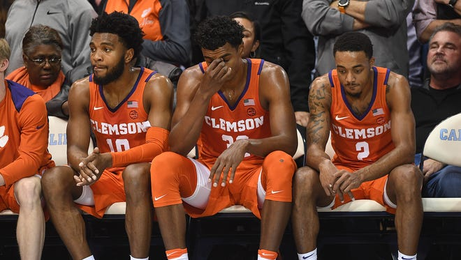 From left, Clemson guard Gabe DeVoe (10), forward Donte Grantham (32), and guard Marcquise Reed (2) sit on the bench during the closing seconds of the Tigers 87-79 loss to North Carolina on Tuesday, January 14, 2018 at UNC's Smith Center in Chapel Hill, N.C.