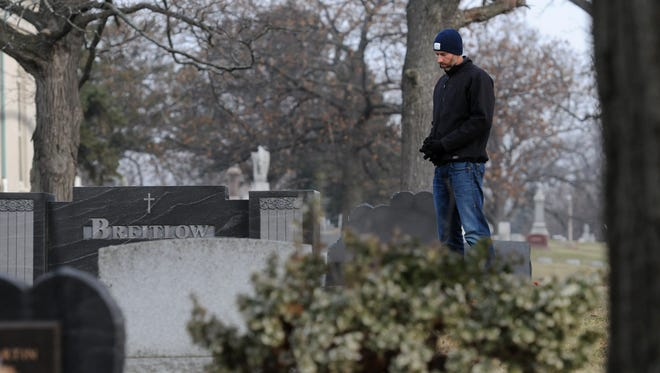 Jay Breitlow reflects at the grave of his father at Wauwatosa Cemetery Friday, Dec. 5, 2014. His father Dale Breitlow, associate principal at Wauwatosa West High School was shot and killed in 1993. Breitlow talks about the national school walkouts in the wake of the recent mass school shooting in FL.