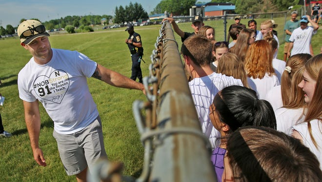 Noblesville West Middle School science teacher Jason Seaman visits with his students, over a fence, at the IHSAA baseball championships, the Noblesville vs Hamilton Southeastern game, Monday, May 28, 2018.  This is the first time his students have seen him since Friday May 25's school shooting.  When a student opened fire in the seventh grade science classroom, Seaman intervened to stop the shooter from shooting more students.  He and one student were shot in the incident.  He was shot three times.  He told the students he couldn't hug them just yet, because he was still a little tender, but he could high five them.