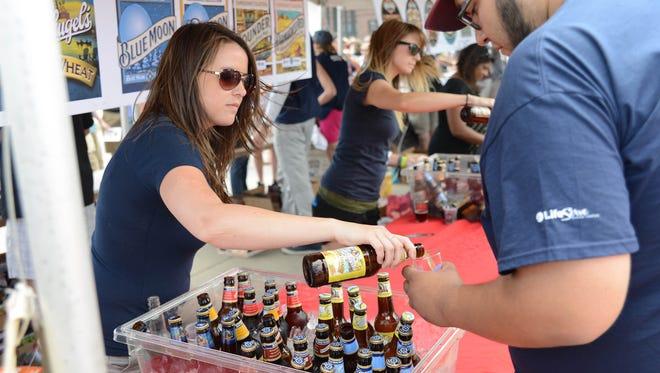 Kara Hall, 26, serves Leinenkugel and Blue Moon beers at The Iowa Craft Brew Festival on Saturday June 14, 2014.