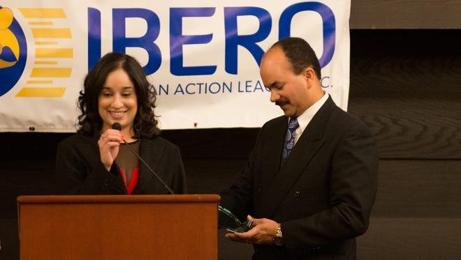 Assistant Director of Multicultural Affairs & Diversity Programs at St. John Fisher College Juana L. Vega receives the Ibero Alicia Torres Award from Ibero Board President Juan Lugo.