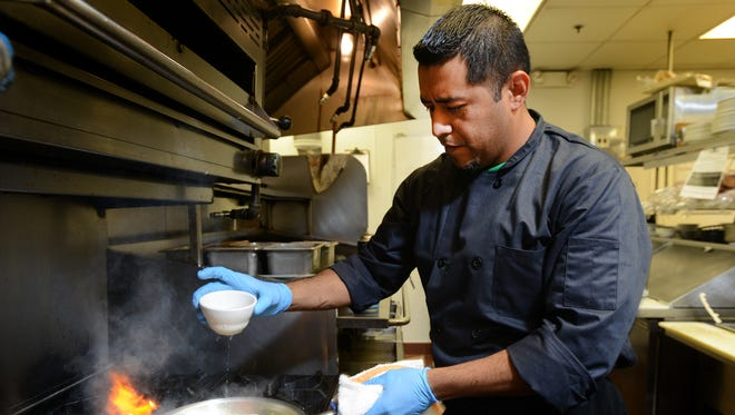 Irish Eyes Chef Juan Escamilla prepares the restaurant's Seafood Shepherd Pie recently at the Lewes restaurant.