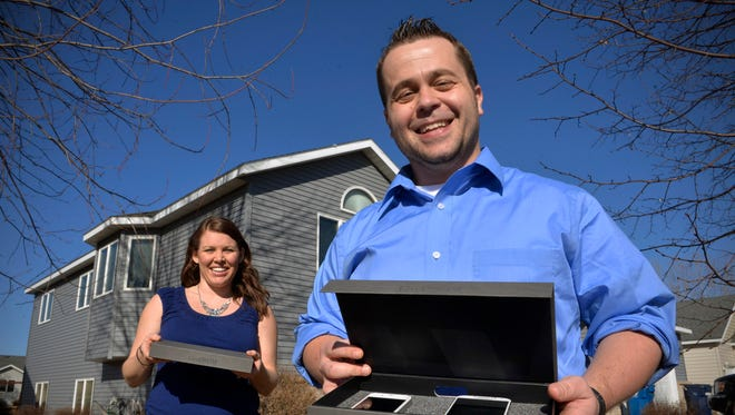 Sartell resident Mitch Bain and his wife, Savanna, hold the OSOMBOX product on March 10. The device is basically a padded container for smartphones with a hole for charging cords that can be used as a tool to remind families to carve time out time together free from the phone's distractions.