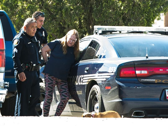 A woman is handcuffed and placed in the back of a Las Cruces police until on Monday, March 21, 2016,  after a stabbing occurred at the Imperial Sky Motel located on West Picacho Avenue.