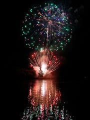Fireworks reflect on the surface of the Cumberland