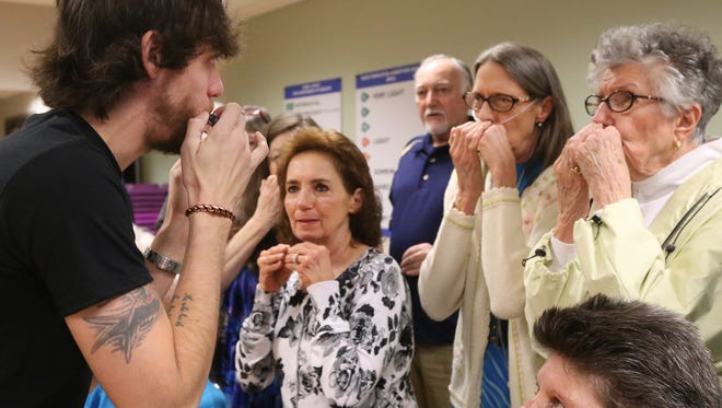 Country music artist Chris Janson, left, plays harmonica with a group of COPD patients on Wednesday, March 9, 2016. Mary Ann Maynard, left, Glenda Greene and Gladys Smith join in as  they play harmonica with Janson. Judy Green listens at far right. Janson spoke about how he learned to breathe better when he learned to play the harmonica.
