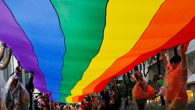 Participants raise a rainbow flag, a symbol of the gay rights movement, on Nov. 8, 2014.