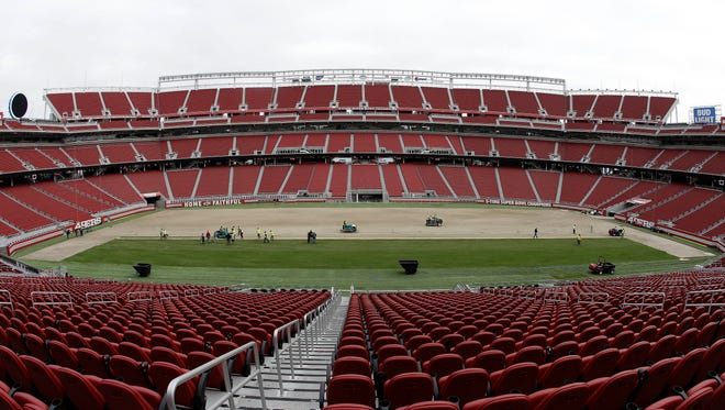 In this photo taken with a fisheye lens, workers install sod on the field at Levi's Stadium in preparation for the NFL's Super Bowl 50 in Santa Clara, Calif., Monday, Jan. 11.