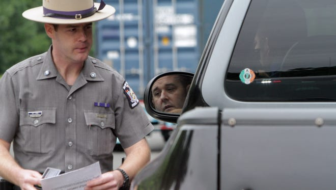 A ticket might be the least consequence for distracted driving. A State Trooper talks to a motorist who was using a cellphone while driving along Interstate 684 in Somers. File photo.