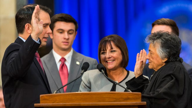 Wisconsin Gov. Scott Walker, left, takes the oath of office from Shirley Abrahamson, Chief Justice of the Wisconsin Supreme Court, during Walker's inauguration ceremony at the Capitol on Monday. in Madison. Pictured behind the governor are his son Alex and wife, Tonette.