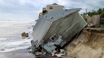 In this Monday, Sept. 11, 2017, file photo, a house slides into the Atlantic Ocean in the aftermath of Hurricane Irma at Ponte Vedra Beach, Fla.