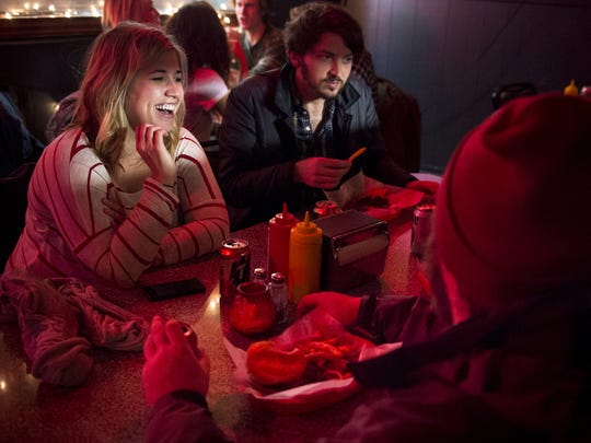Lindsay Hayes, left, and Warren Givens, right, chat with friends at Dino's, on Feb. 24.