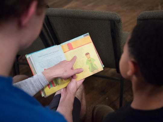 Luke Eldredge, a sophomore at Furman, reads with Terry Black, 7, at the Frazee Dream Center in Greenville on Tuesday, October 4, 2016.
