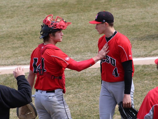 Former Cathedral High School players Bo Schmitz, left, and Dominic Austing, right, talk on the field this season. Schmitz is hitting .347 and Austing is 6-2 for the Huskies.