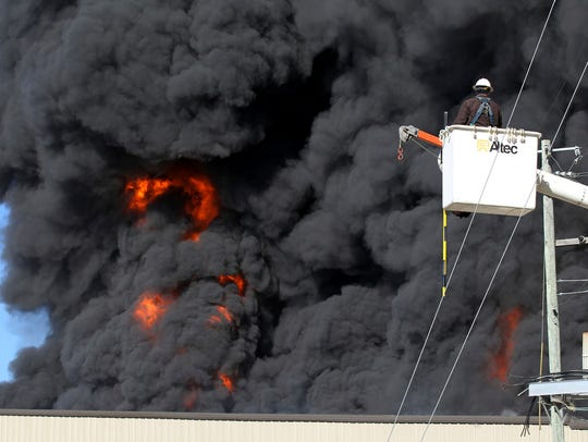 A Pontotoc Electric Company worker watches the blaze