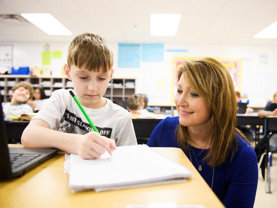 Suzanne Billings helps Jackson Mason, 10, with his