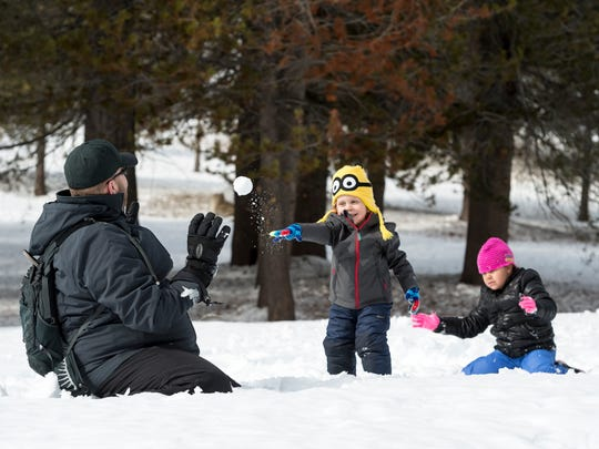 Tony Berryman of Los Angeles, left, plays in the snow with his son Ronny Berryman, 3, and daughter Isabella Berryman, 7, at Wolverton in Sequoia National Park on Friday, March 9, 2018.