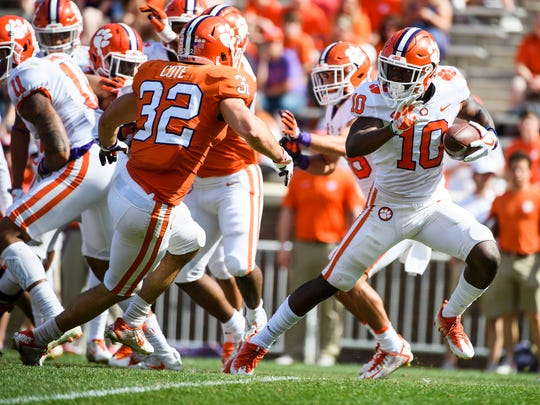 Clemson wide receiver Derion Kendrick (10) attempts to evade linebacker Justin Foster (35) during the 2018 spring football game on Saturday, April 14, 2018.